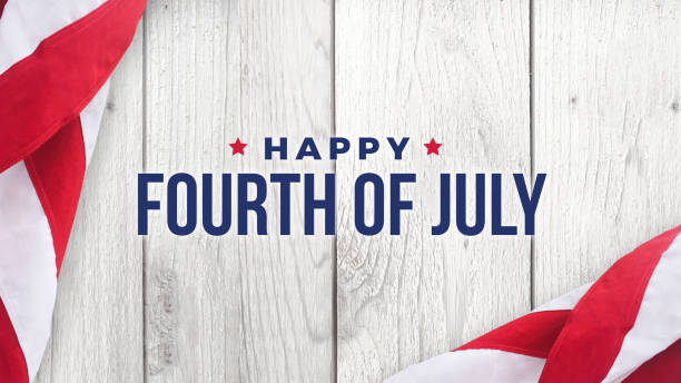 Happy Fourth of July Text Over White Wood and American Flags stock photo