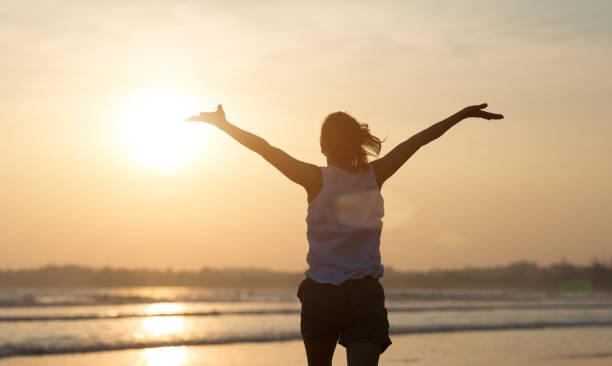 Happy Free Woman bei Sonnenuntergang am Strand – Foto