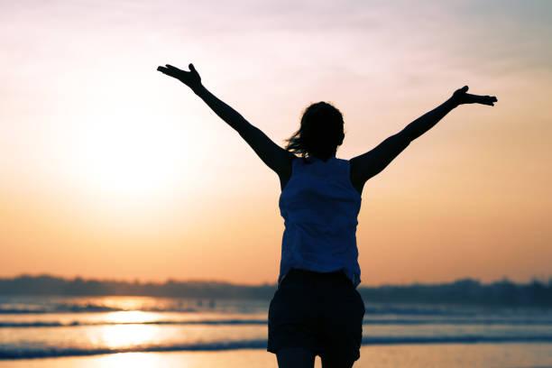 Glückliche freie Frau bei Sonnenuntergang am Strand – Foto