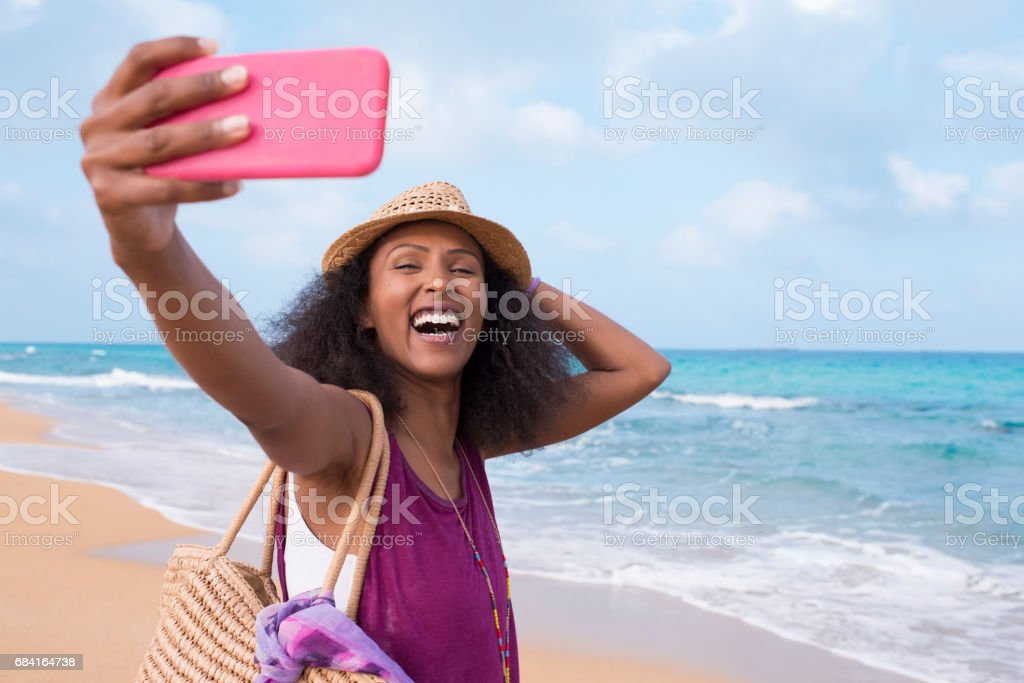 Happy free woman with positive emotion taking selfie on tropical beach. royalty-free stock photo