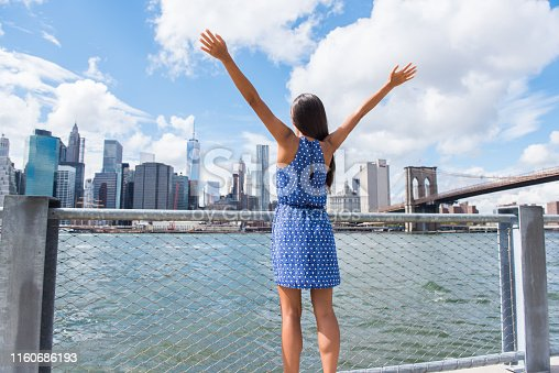 Happy free woman cheering at NYC New York city urban skyline with arms up raised in the sky. Success in business career, goal achievement or carefree freedom successful urban person concept.