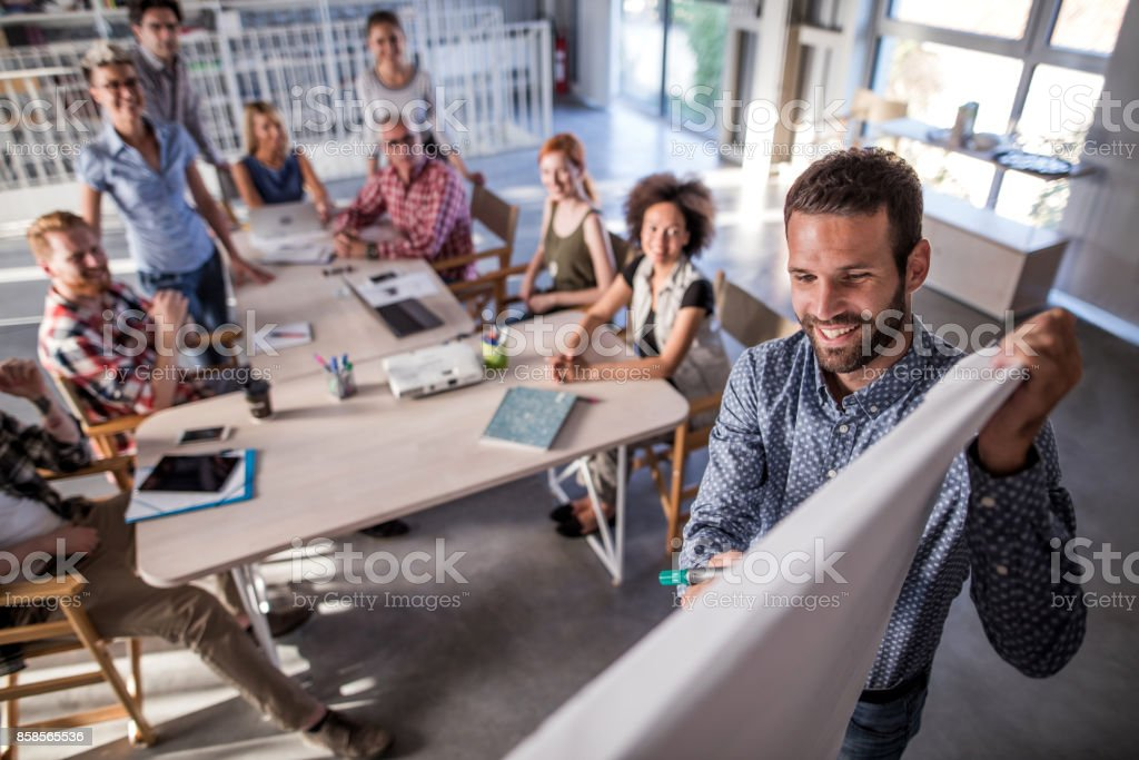 Happy freelancer writing a business plan on whiteboard during a presentation in the office. stock photo