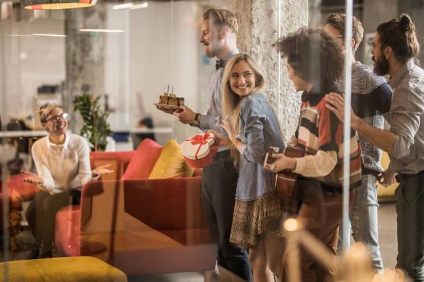 glücklich freelancer überraschend ihre kollegin zum geburtstag im büro. - gitarren geburtstagstorten stock-fotos und bilder
