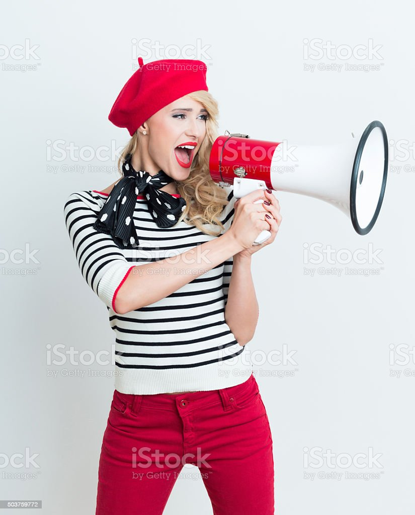 Happy french woman wearing red beret shouting into megaphone Portrait of excited beautiful blonde woman in french outfit, wearing a red beret, striped blouse and neckerchief, shouting into megaphone. Adult Stock Photo