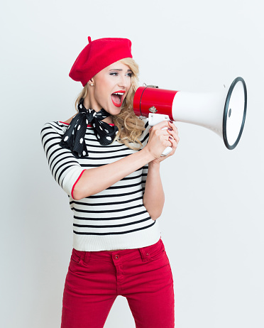 Happy French Woman Wearing Red Beret Shouting Into Megaphone Stock Photo - Download Image Now