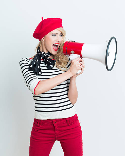 Happy french woman wearing red beret shouting into megaphone stock photo