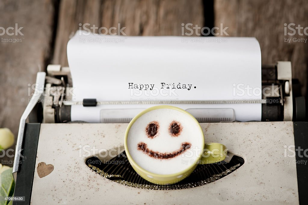 Happy Friday on typewriter with coffee cup, stock photo
