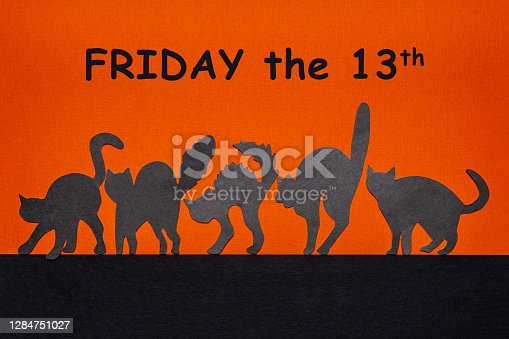Happy Friday the 13. Black funny wild cat silhouettes on orange and black background. Day of bad luck, failure, horror concept. Text FRIDAY THE 13TH.