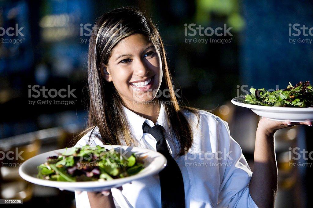Happy friendly hispanic waitress serving salads stock photo