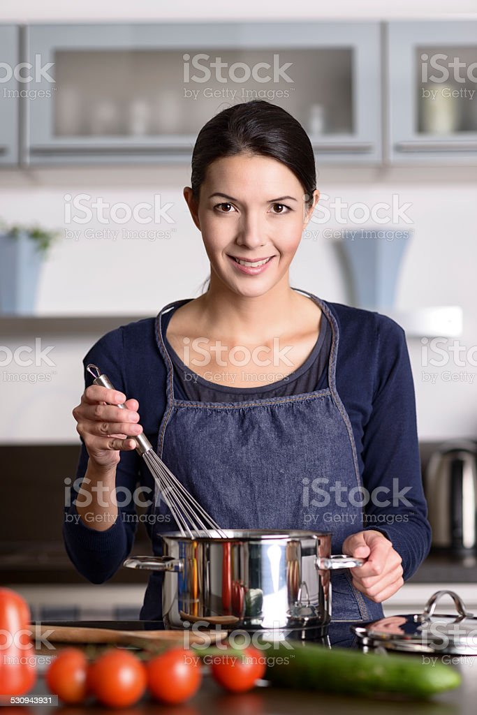 Happy friendly young housewife cooking dinner stock photo