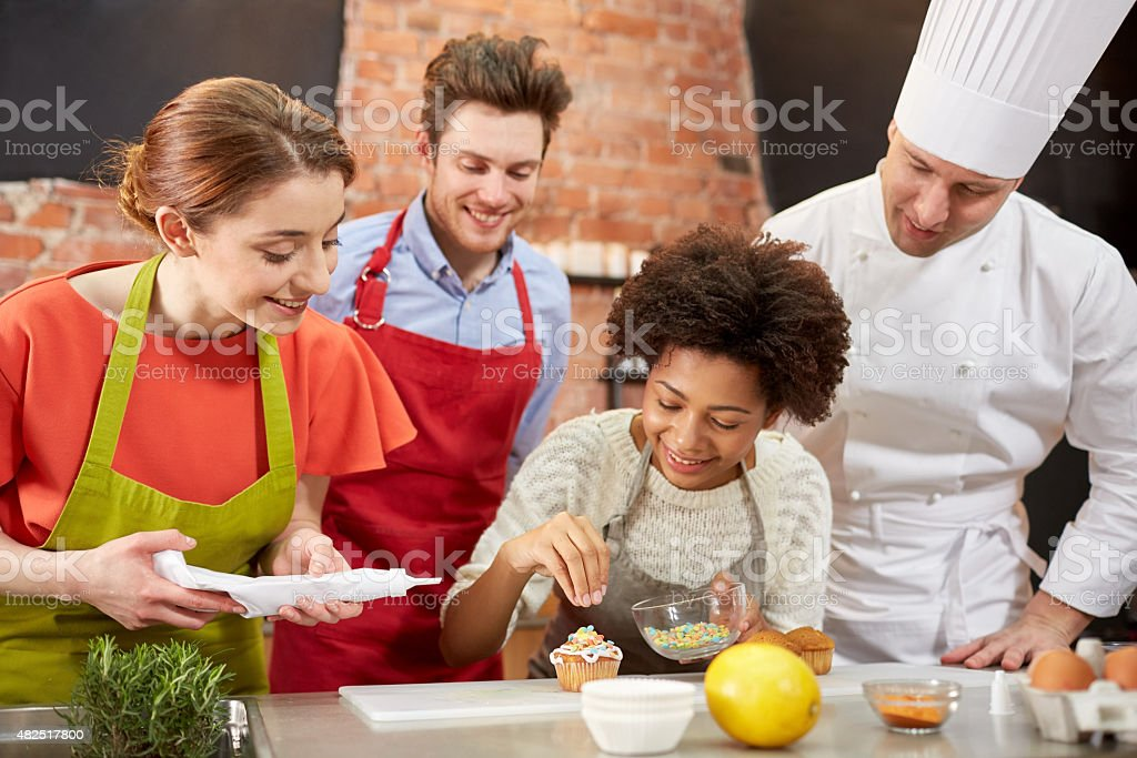 happy friends and chef cook baking in kitchen stock photo