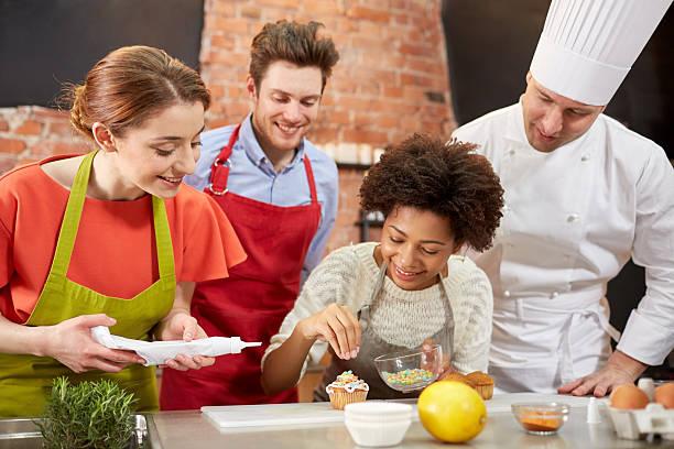 felici amici e lo chef cucinare cottura in cucina - compagni scuola foto e immagini stock