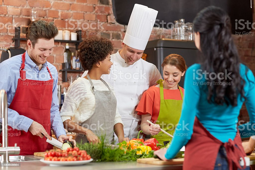 happy friends and chef cook cooking in kitchen stock photo