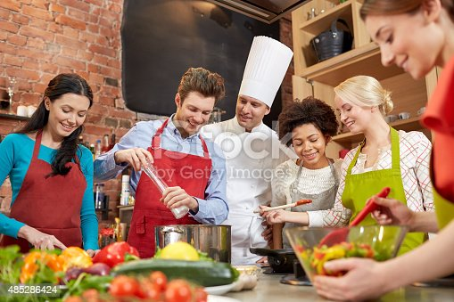 488109116istockphoto happy friends and chef cook cooking in kitchen 485286424