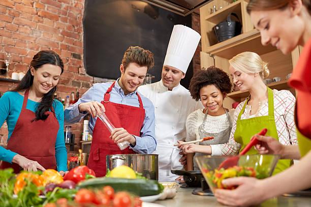 felici amici e lo chef cucina piatti in cucina - compagni scuola foto e immagini stock