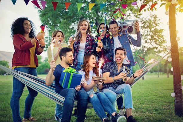 glückliche freunde feiert geburtstag im park und machen spaß - musik kuchen stock-fotos und bilder