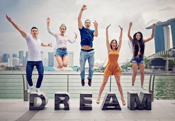 glückliche freunde sind genießen erfolg springen. - traum team stock-fotos und bilder