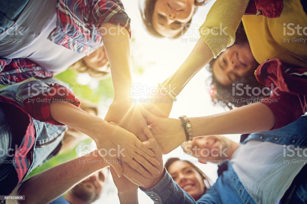 Happy friends are looking their united hands stock photo