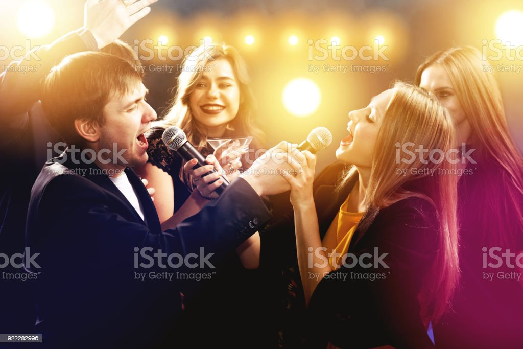 Amigos felices están cantando y bailando en discoteca - foto de stock