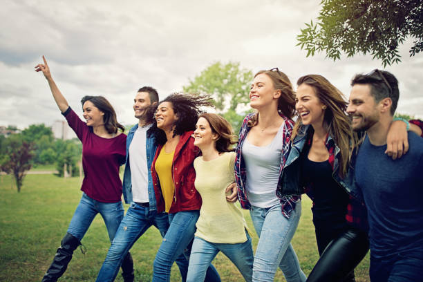 Happy friends are wlaking ahead arm in arm stock photo