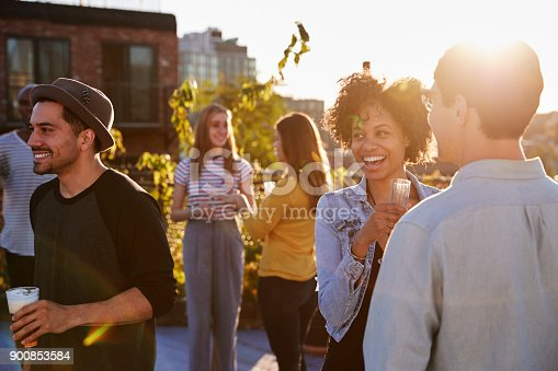 istock Happy friends at a rooftop party backlit by sunlight 900853584