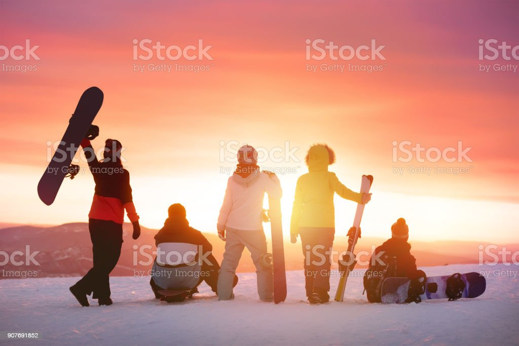 Amis heureux à la station de ski contre le coucher de soleil photo libre de droits