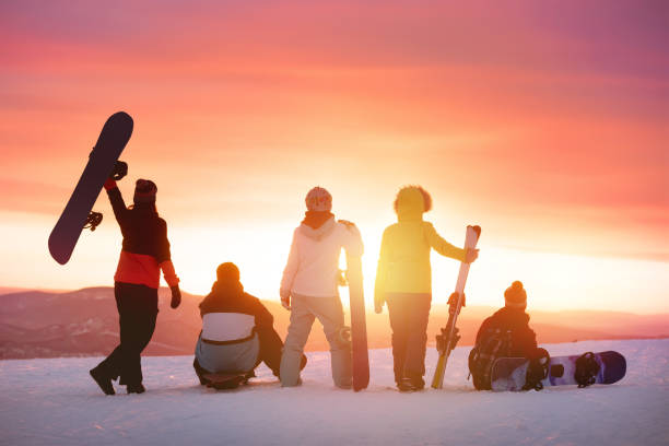 Happy friends at ski resort against sunset Happy friends with ski and snowboard at ski resort against sunset ski stock pictures, royalty-free photos & images