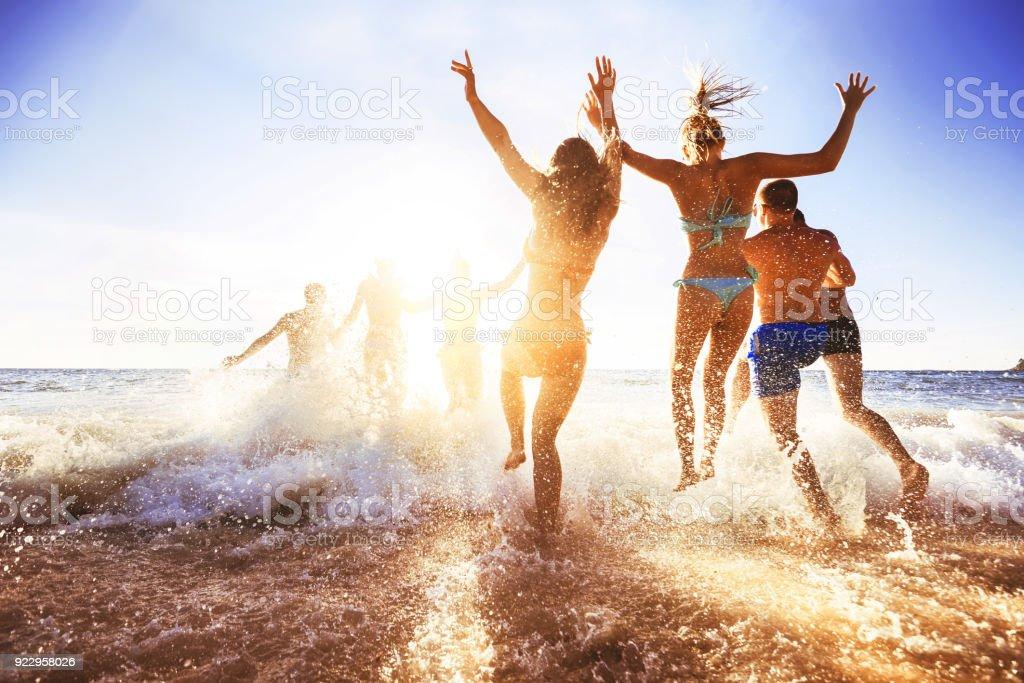 Amigos felices en la playa al atardecer - foto de stock