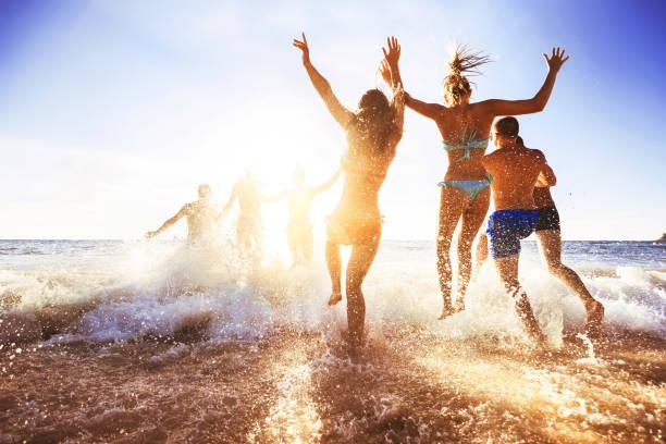 happy friends at sunset sea beach - nuoto mare foto e immagini stock