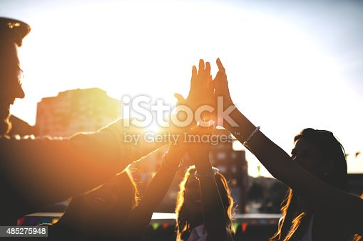 istock Happy friends at the rooftop doing high five 485275948