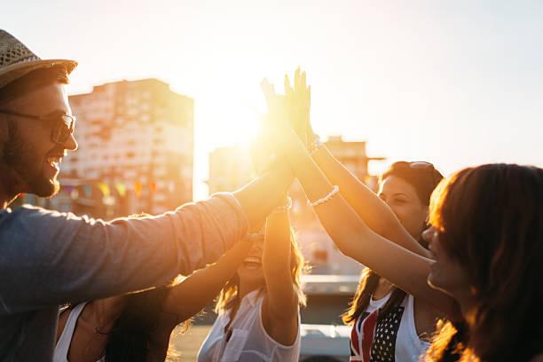 Amici felici sul tetto facendo alta cinque - foto stock