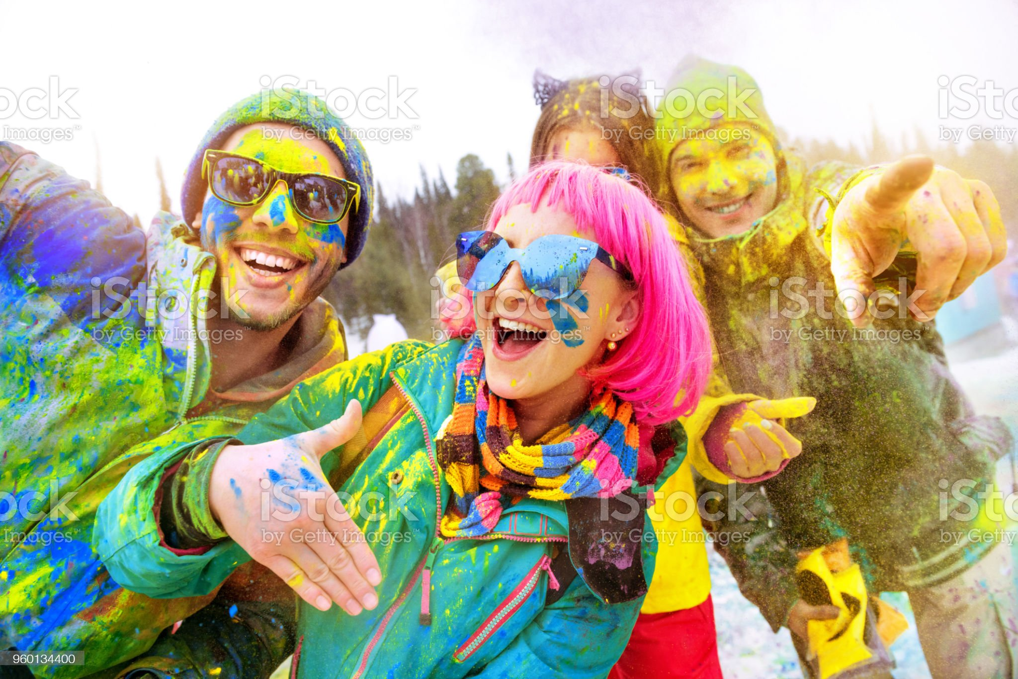Happy friends at winter holi colors festival royalty-free stock photo