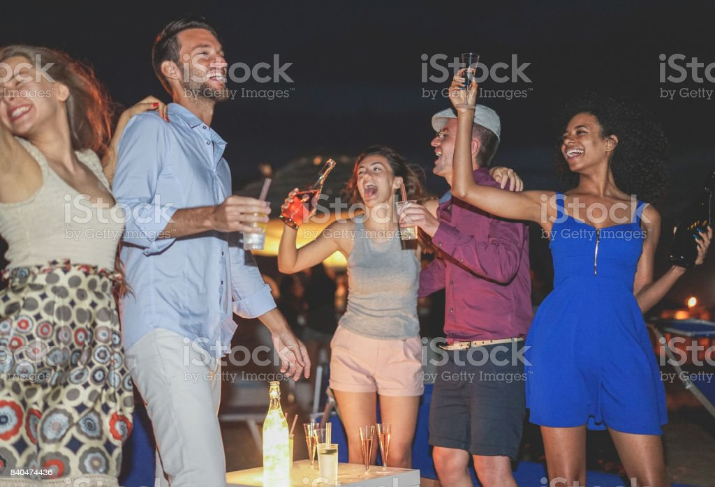 Happy friends celebrating at beach party outdoor drinking champagne and tropical cocktails - Young people having fun at nightclub next to the ocean - Main focus on right girl face - Summer concept stock photo