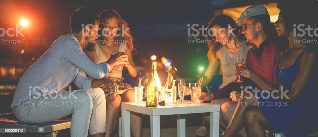 Happy vrienden vieren tijdens de avond strand partij buiten drinken champagne - jonge mensen plezier bij bar volgende naar de oceaan - Soft focus op center flessen - jeugd levensstijl en foto
