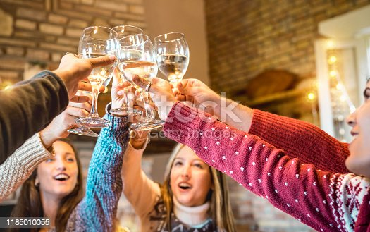 1064325668istockphoto Happy friends celebrating Christmas toasting champagne wine at home dinner - Winter holiday concept with young people enjoying time together having fun at log cabin - Warm filter with focus on glasses 1185010055