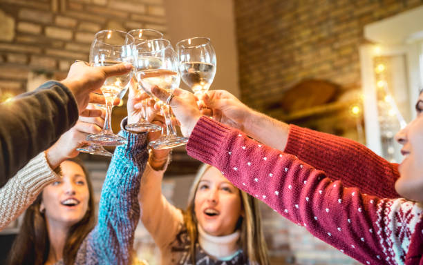 Happy friends celebrating Christmas toasting champagne wine at home dinner - Winter holiday concept with young people enjoying time together having fun at log cabin - Warm filter with focus on glasses stock photo