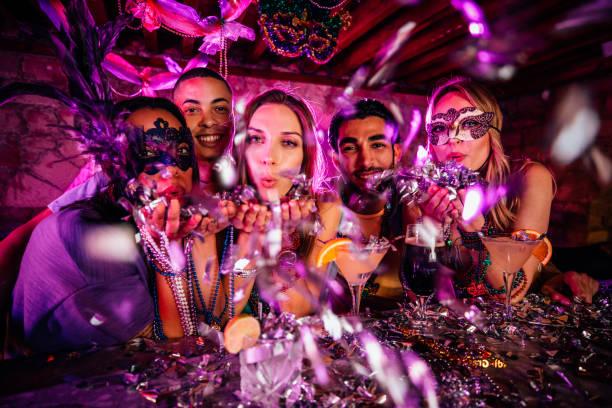 glückliche freunde feiern karneval und bläst konfetti auf party - bier kostüm stock-fotos und bilder