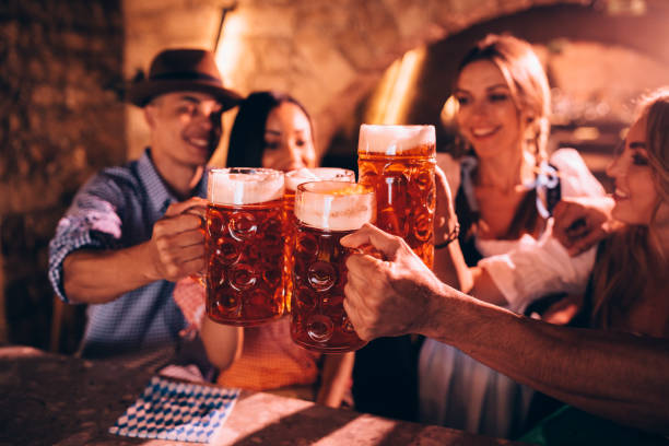 happy friends celebrating oktoberfest and toasting with beer - german culture stock pictures, royalty-free photos & images