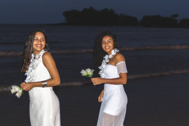 Happy friends celebrating reveillon on the beach, offering white flowers. Paraiso beach, Mosqueiro Happy friends celebrating reveillon on the beach, offering white flowers. They wear white clothes. Two young women enjoying and partying together. Happiness, togetherness, youth and new year's eve concepts. Paraiso beach, Mosqueiro reveillon stock pictures, royalty-free photos & images