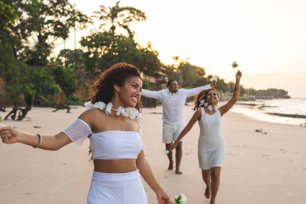 Happy friends celebrating reveillon on the beach, running and holding white flowers. Paraiso beach, Mosqueiro Happy friends celebrating reveillon on the beach, running and holding white flowers. They wear white clothes. Group of young people enjoying and partying together. Happiness, togetherness, youth and new year's eve concepts. Paraiso beach, Mosqueiro reveillon stock pictures, royalty-free photos & images