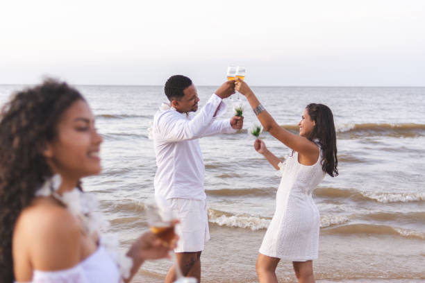 Happy friends celebrating reveillon on the beach toasting with glasses of wine. Paraiso beach, Mosqueiro Happy friends celebrating reveillon on the beach toasting with glasses of wine. They wear white clothes. Group of young people enjoying and partying together. Happiness, togetherness, youth and new year's eve concepts. Paraiso beach, Mosqueiro reveillon stock pictures, royalty-free photos & images