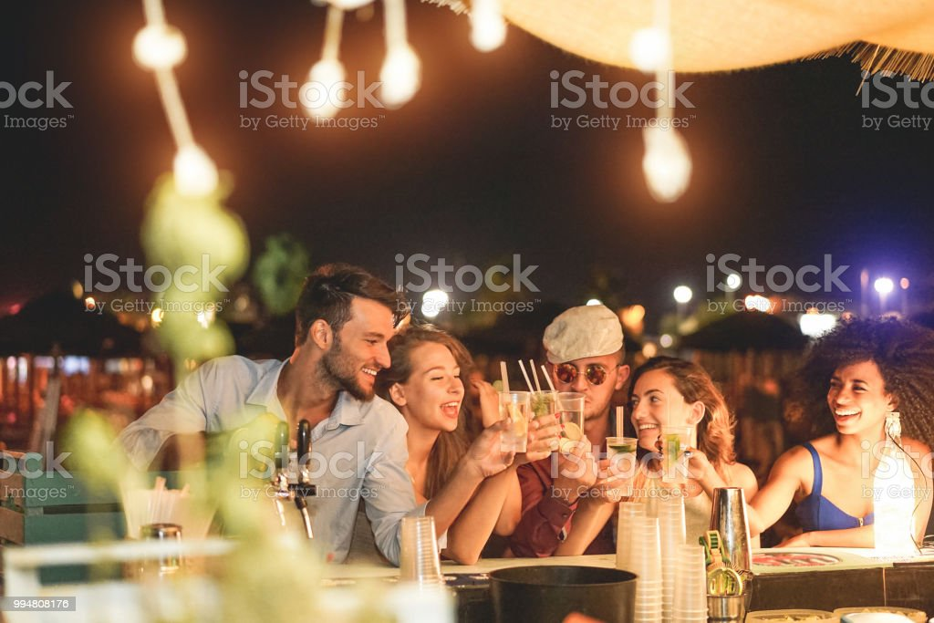 Happy friends cheering and drinking cocktails at beach party outdoor - Young millennials people having fun at weekend summer night - Youth lifestyle and nightlife concept - Main focus on left guys stock photo