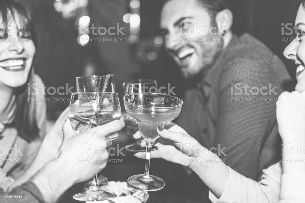Happy friends cheering at cocktail jazz bar - Young trendy people having fun drinking alcohol and laughing - Party concept - Focus on right woman hand glass - Black and white editing - Warm filter stock photo