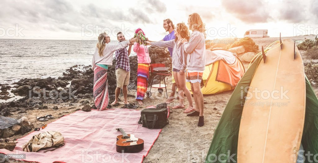 Happy friends cheering with beers at barbecue picnic next to the ocean - Surfers people having fun and laughing together during sport holidays - Travel, vacation, party and friendship concept stock photo
