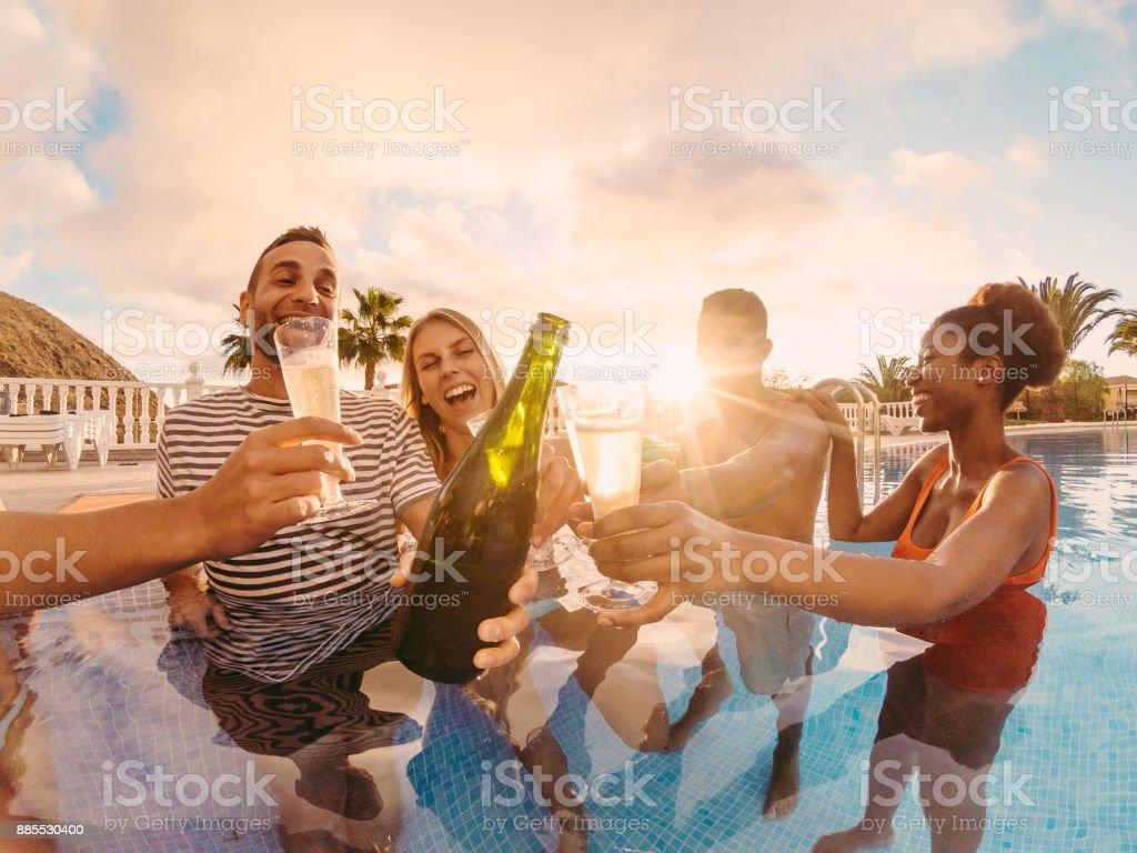 Glückliche Freunde jubeln mit Champagner im Pool-Party bei Sonnenuntergang - reiche Leute Spaß in exklusiven tropischen Urlaub - Urlaub und Freundschaft Konzept - Schwerpunkt linken Mann - Töne Sonnenfilter – Foto
