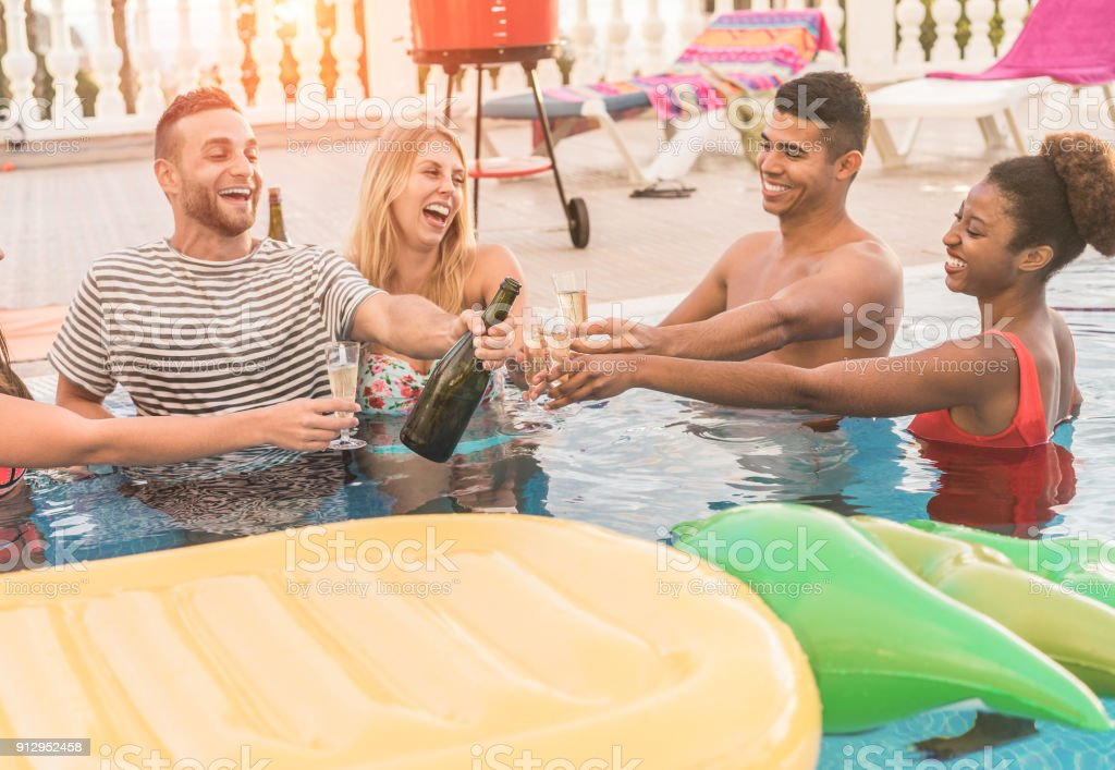 Happy friends cheering with champagne in pool party at sunset - Rich people having fun in exclusive tropical vacation outdoor- Holiday, youth lifestyle and friendship concept - Focus on glasses stock photo