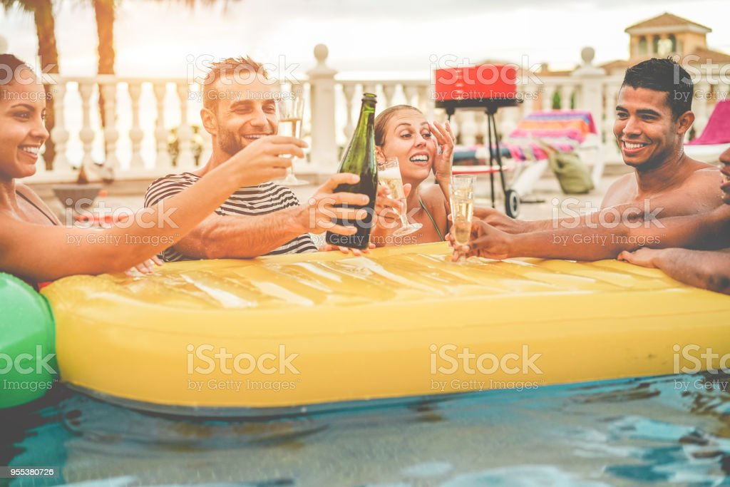 Happy friends cheering with champagne in pool party at sunset - Rich people having fun in tropical vacation outdoor - Holiday, youth lifestyle and friendship concept - Focus on center guys faces stock photo