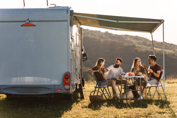 Happy friends communicating at picnic table by the camp trailer in summer day. stock photo
