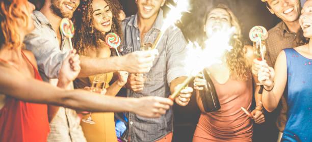 glückliche freunde tanzen und trinken champagner party nacht - junge leute, die spaß mit wunderkerzen-feuerwerk im night-club - jugend und freundschaft konzept - schwerpunkt lockiges haar mädchen gesicht - new york new year stock-fotos und bilder