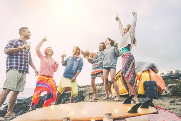 glückliche freunde tanzen und haben spaß machen eine beach party in der campingplatz - junge menschen lachen und trinken bier beim camping nächsten ozean - reisen, urlaub, jugend-lifestyle-konzept - tanz camp stock-fotos und bilder